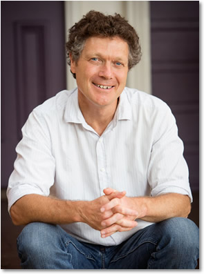 Hugh Churchward sits with his elbows resting on his knees and has a relaxed and friendly smile.